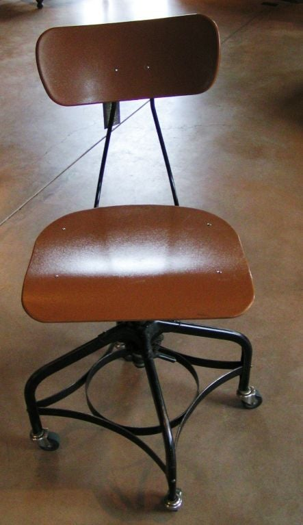 Pair of adjustable Toledo Metal Furniture Co. chairs for drafting, office, or university, circa mid 20th century.   Tan plastic with black metal base; chairs are on casters with adjustable seat height and back support. Chair bases are locked