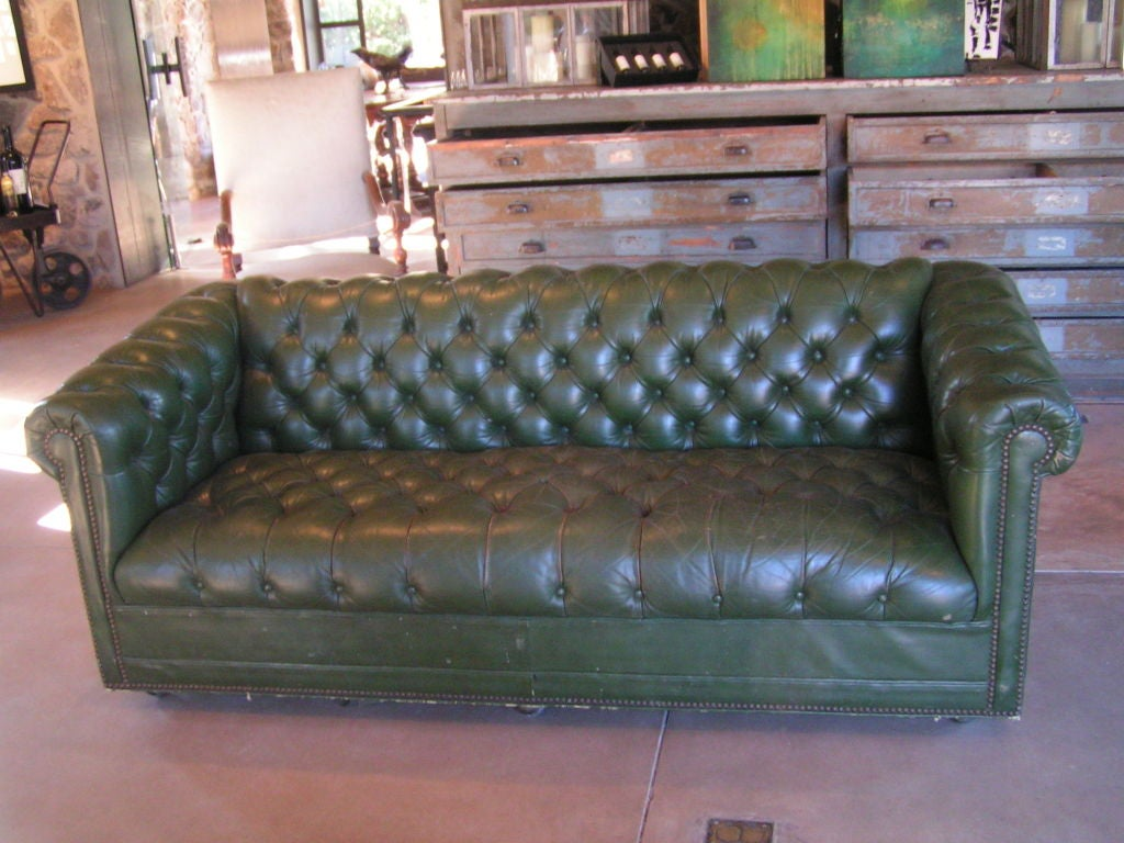 Beautiful green leather tufted sofa.  Has a gorgeous patina, nailhead details and is very comfy.  The front has casters and the back has legs.