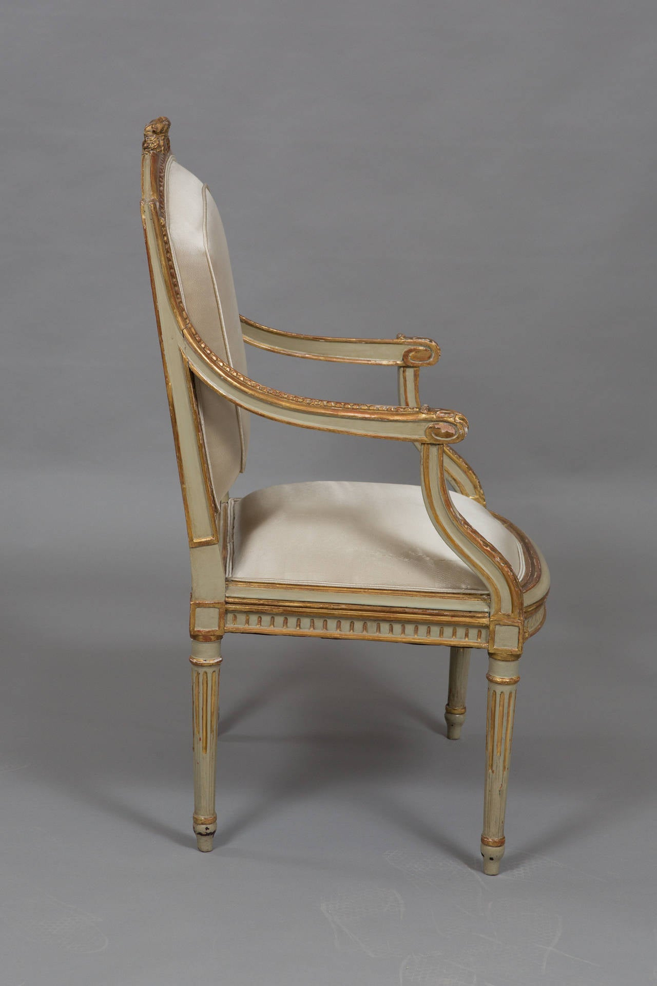 Louis XVI style parcel gilt armchair with original paint and gilt. Newly upholstered in grey silk. Acanthus detail on the supports. 
