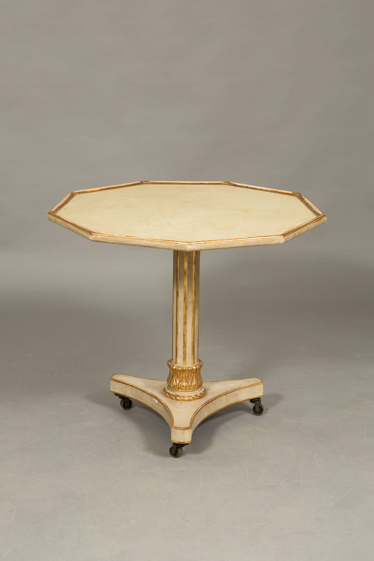9-sided Neoclassical style parcel gilt center table on casters with antique painted finish. From the estate of Brooke Astor.