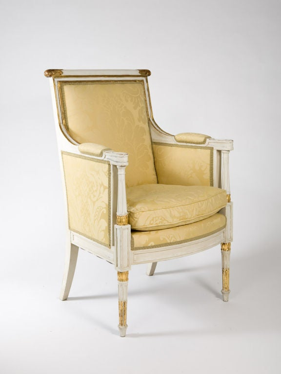 White painted Louis XVI style bergere with gilt painted accents, and cream damask upholstery. Late 19th - early 20th century.<br />