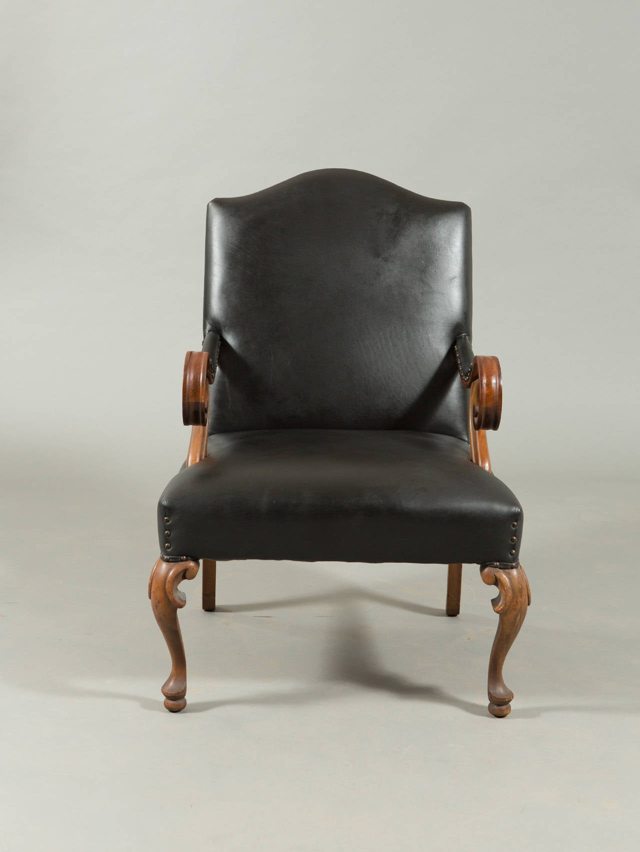 Hand-carved walnut Louis XVIII style armchair with curved wood and tapered legs and brass nailhead trim. Seat depth - 20