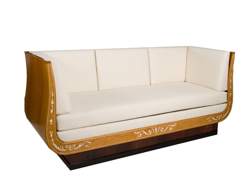 Elegant sofa designed by Carl Malmsten (1888-1972) and retailed by Nordiska Kompaniet. Classical form with gracefully curved sides and open frame back. Burled veneer with ivory/bone inlay, ebonzied molding and fitted cushions. CM brand on underside