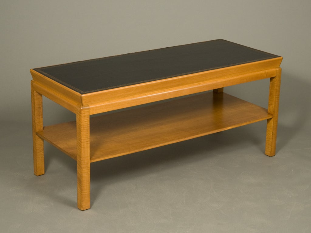 Mid-Century modern oak coffee table with black leather top with gilt embossed border and lower shelf.