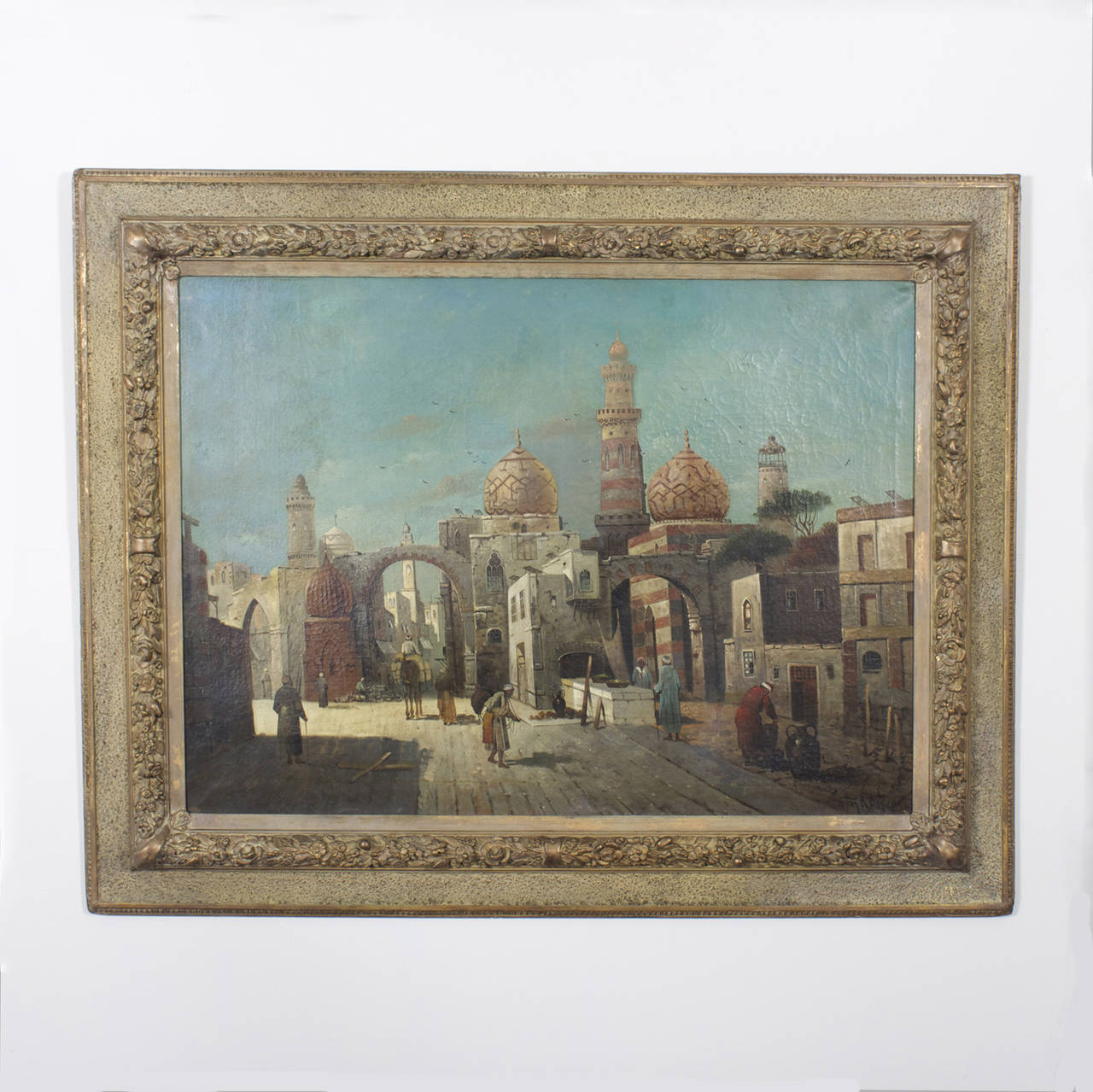 German Orientalist oil on canvas painting of a street scene. Long shadows suggesting start of the day, complete with merchants, travelers, arches, onion domes and cupolas all set against a brilliant blue sky. Signed Anton Hubner in the lower right.
