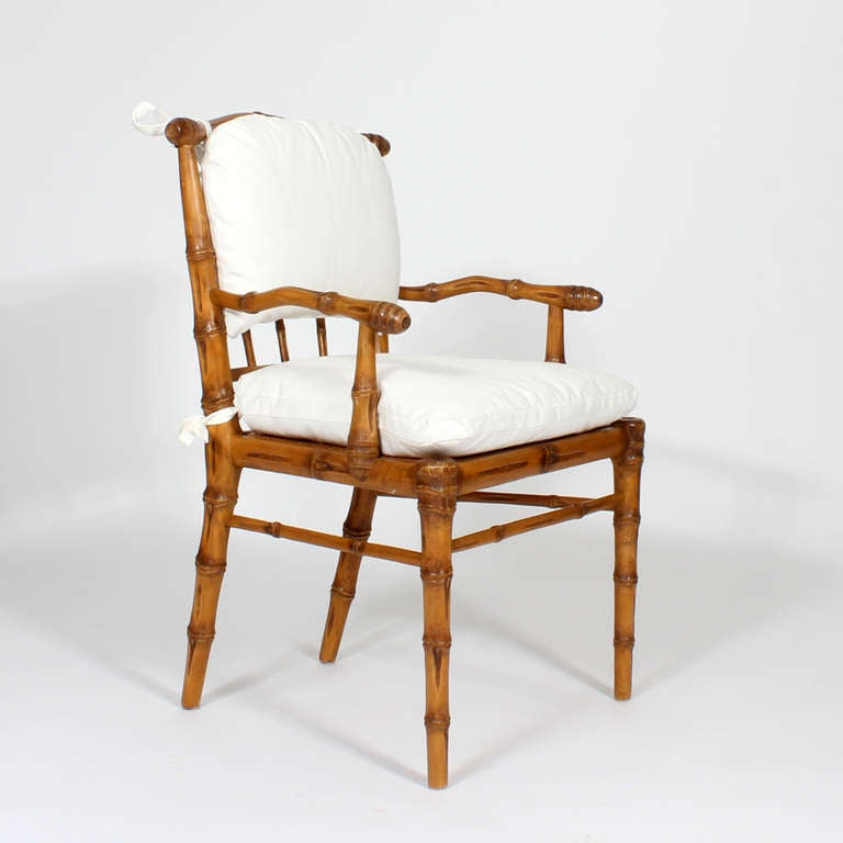 of eight carved faux bamboo dining chairs with back and seat cushions