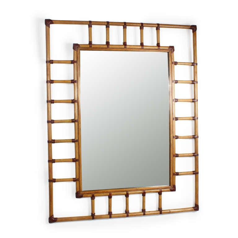 A very large rectangular rattan mirror with leather binding. Possibly McGuire. Great impact on the wall.