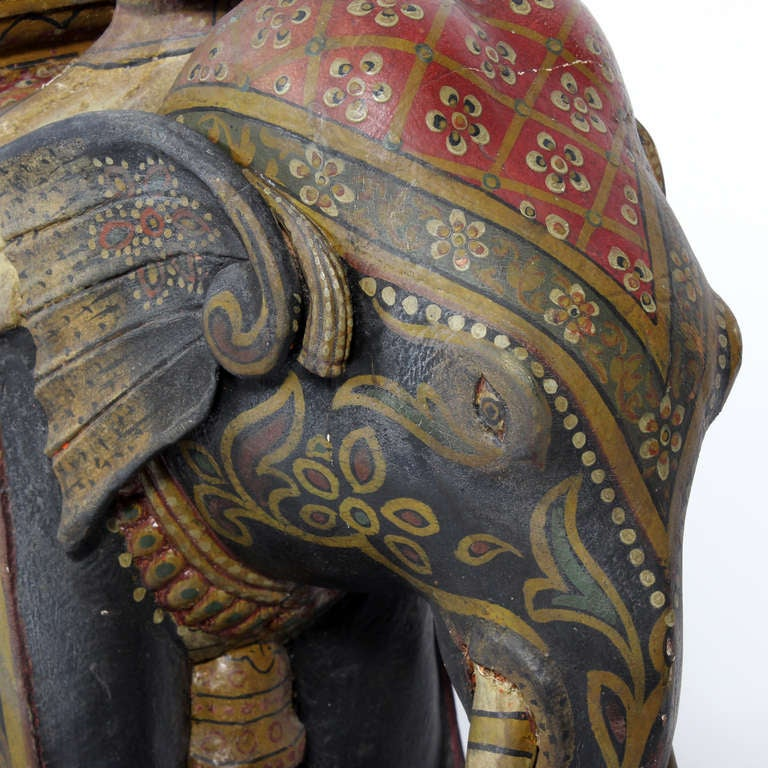 A wonderful paint decorated carved wood Indian elephant with rider on a red painted wheeled base. Incredible detail to the paint. A large-scale, impressive and delightful piece.