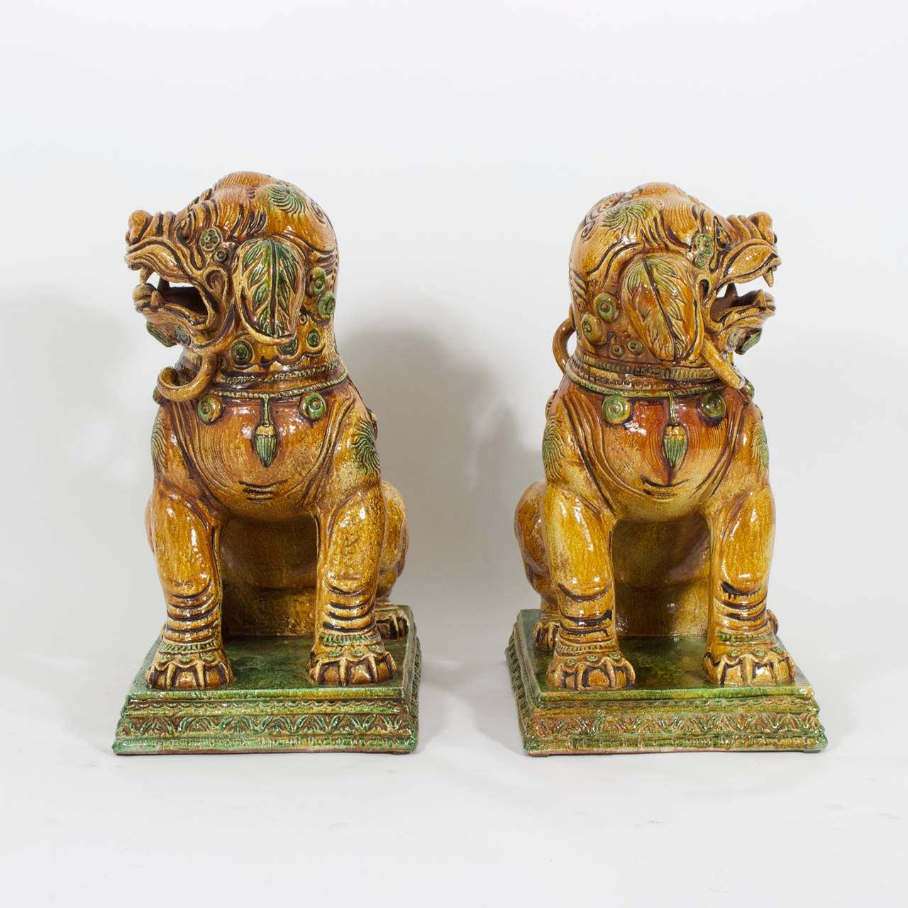 Impressive large true pair of Italian, glazed terra cotta or Majolica foo dogs with subdued colors, powerful stance and just the right touch of whimsy . Traditional form with Mid-Century pedigree.
