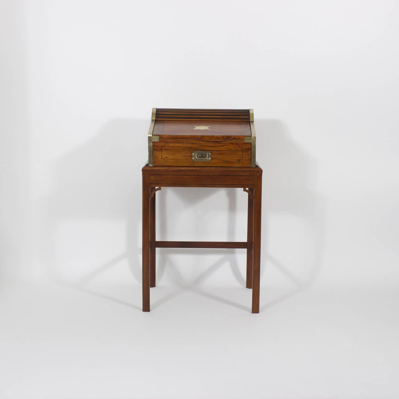 A 19th century diminutive, antique, mahogany campaign roll top desk on stand with brass plaque, brass lined case, string inlay, intriguing pop up hidden compartments, brass recessed campaign hardware and well proportioned custom stand. Newly