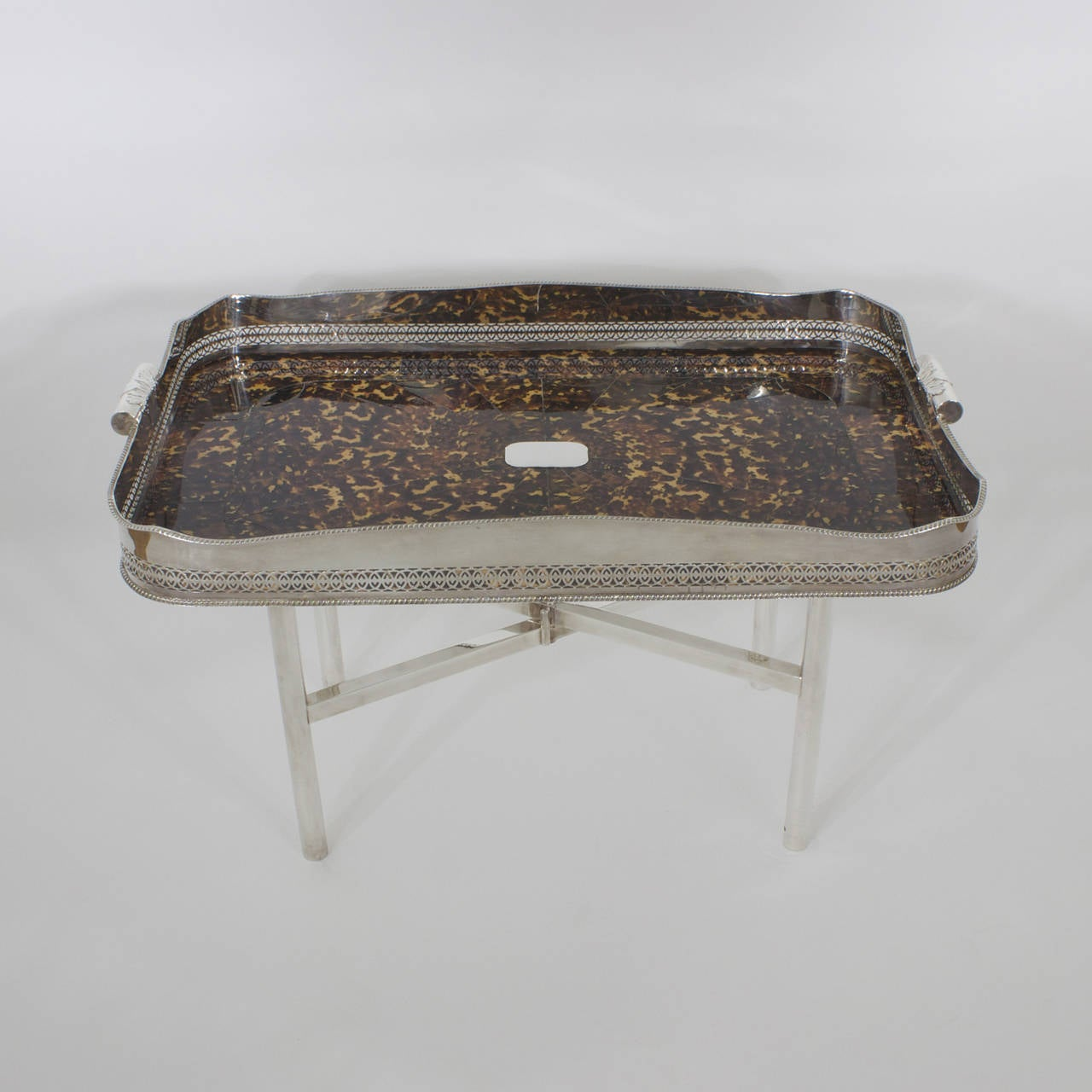 A fine large faux tortoise shell serving tray, tea, coffee, or cocktail table with a prominent silver plated gallery, tooled with intricate fret work, handles decorated with acanthus and center plaque for engraving. This faux tortoiseshell tray is