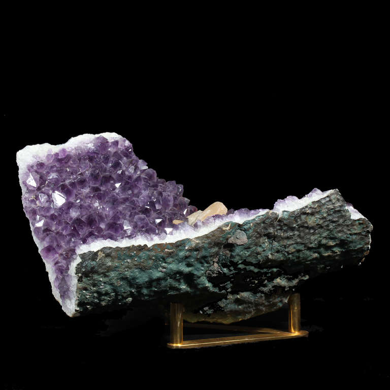 An amethyst geode with a touch of rock crystal, mounted on a tri peg gold plated Stand. Great coffee table piece.