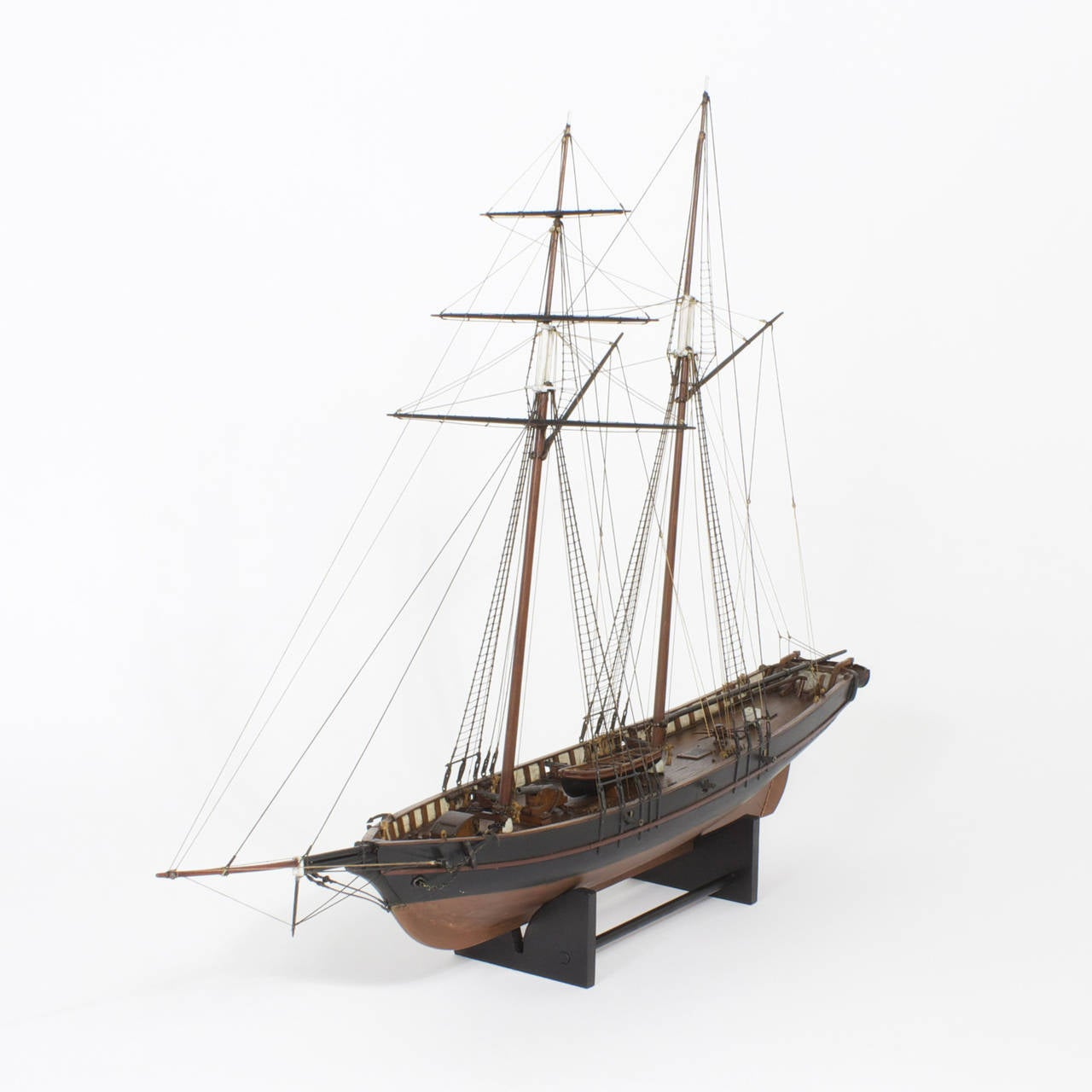 A fine and detailed high quality ship model of a schooner that is rigged for privateering with two masts and a realistic rig. Made of mahogany and trimmed with black and white paint. This model depicts fast moving vessel carrying life boats and 7