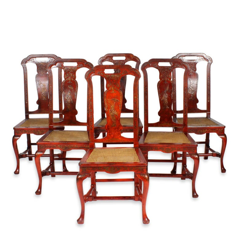 A set of six painted red and gilt chinoiserie decorated dining chairs with caned seats. Queen Anne in form with back splats decorated with females holding umbrellas and top crests with open handles. Cabriole front legs with turned stretchers, and