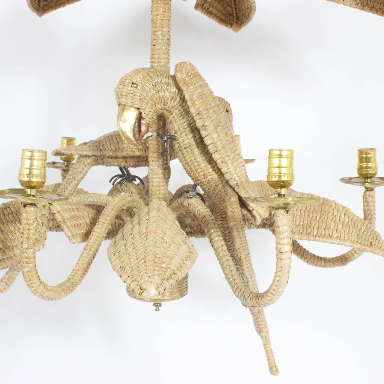 Mario Torres Mid Century 6 light chandelier constructed of an iron frame wrapped with wicker or reed in an intricate tight weave. Featuring 2 busy and playful parrots with brass and copper beaks surrounded by 2 layers of palm fronds creating a fun