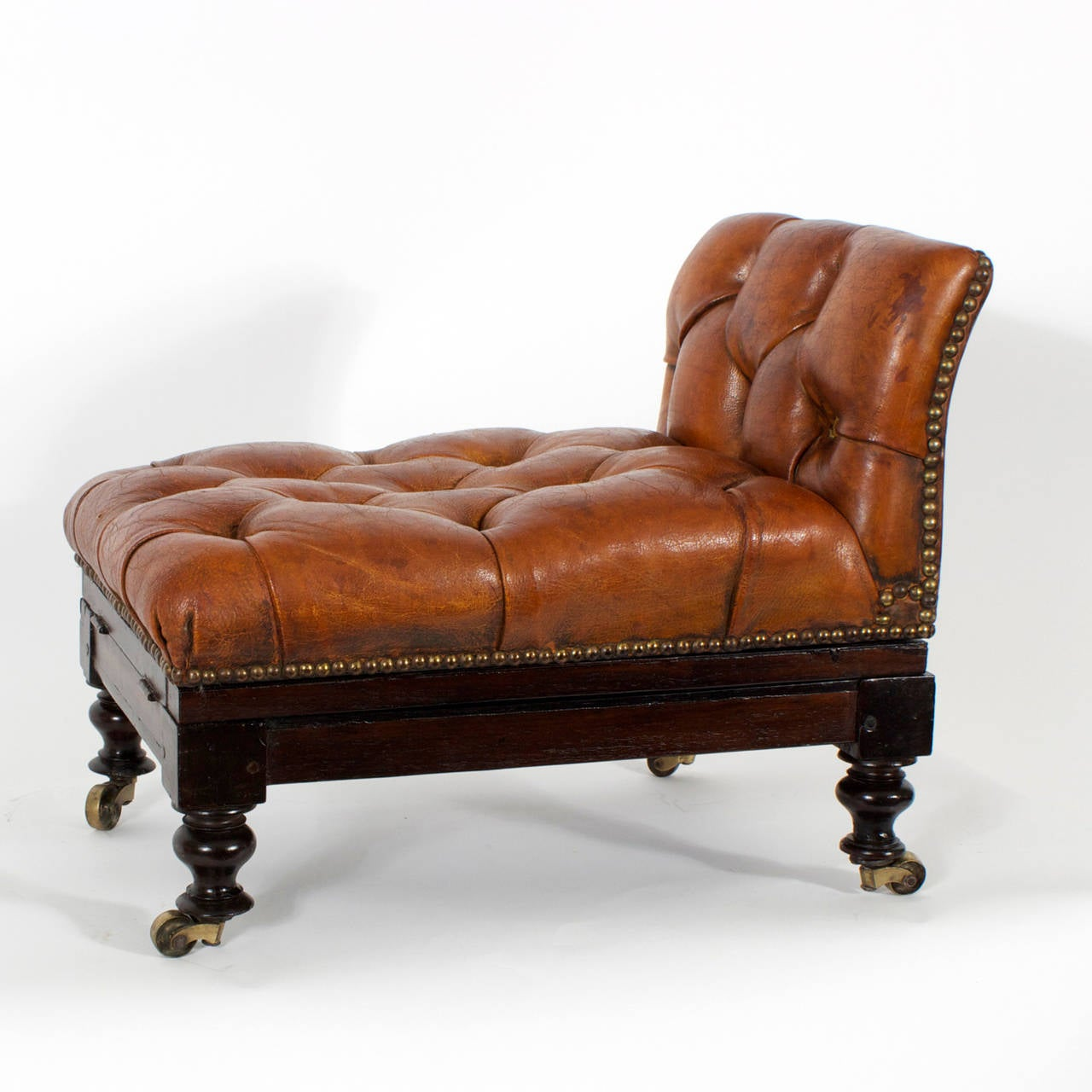 "Here is a fine, 19th century, brown leather, button tufted foot stool with mahogany frame and brass tacks over turned legs and brass wheels. Having the added feature of adjustable angles, of raising 6"", in increments for ultimate comfort."
