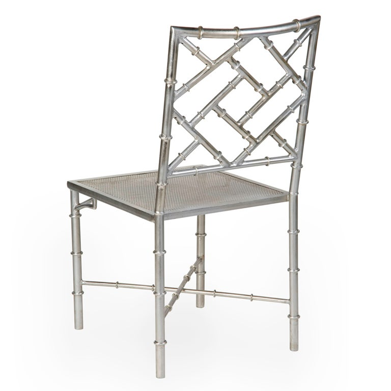 A set of 6 large scale faux bamboo metal chairs in a chrome finish. Faux bamboo backs and legs with Chinese Chippendale features and mesh seats. Custom black cushions are available.