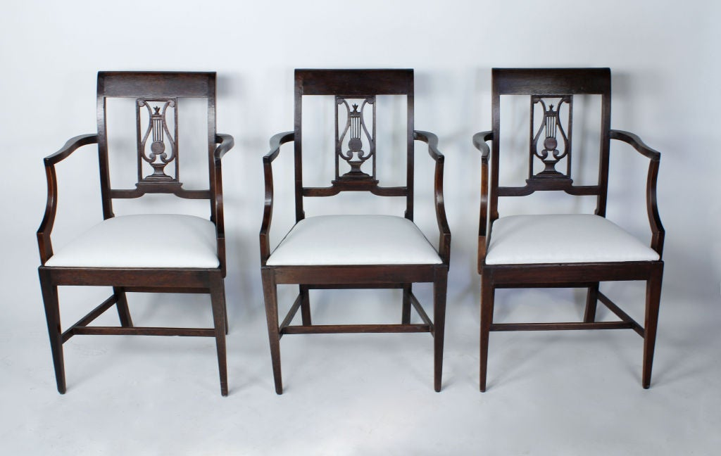 A set of rare neoclassical style dining chairs, comprises of a set of six armchairs with carved lyre motif back splats and H stretcher bases. Walnut. Just add diners.