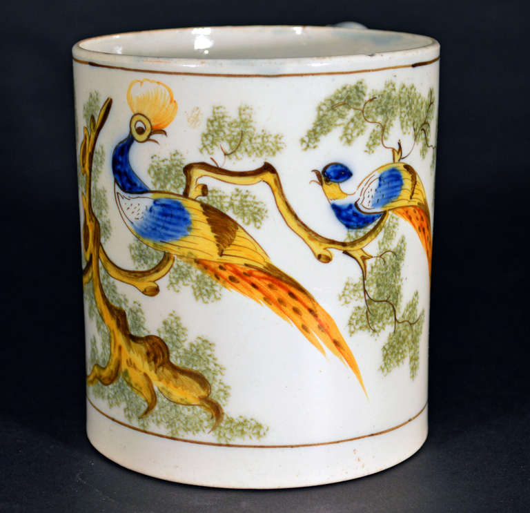 The pearlware peafowl tankard of cylindrical form has a wide double-grooved strap handle with an orange stripe. Two tiny pinholes have been created in the interior base probably as drain holes.  Reference: Illustrated Feathers and Foliage, George