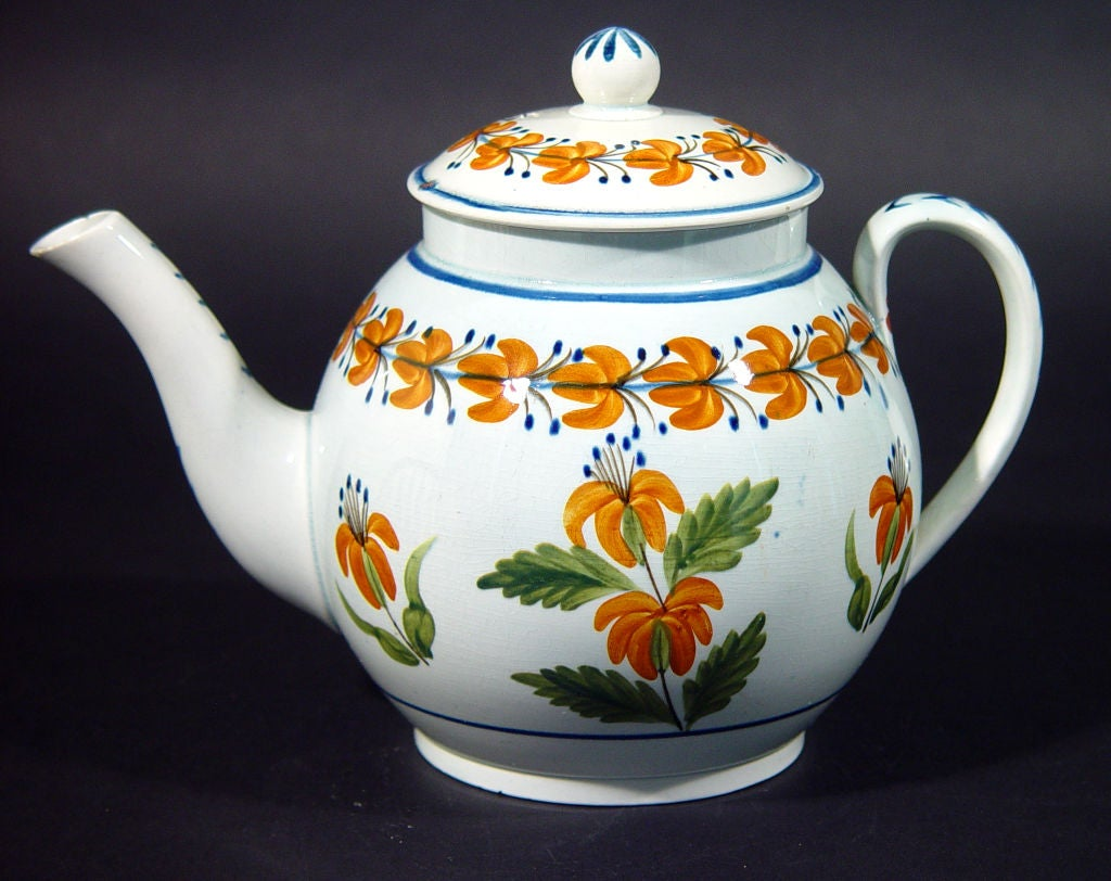 A charming folky fresh pottery teapot decorated with flowers in distinct orange and green.