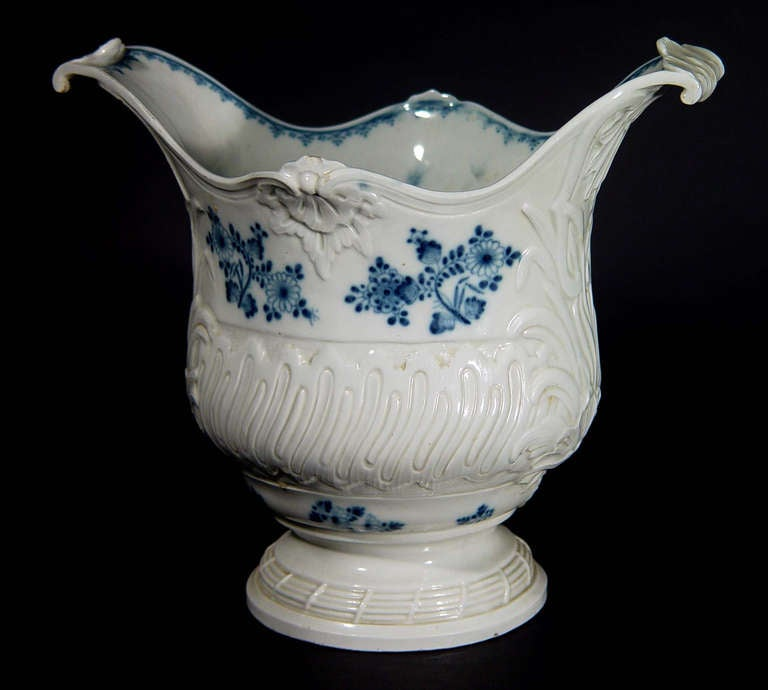 The Rococo Viennese style porcelain wine cooler has a molded band on foot, a deep rounded body with gadroon band, molded leaf and shell design at sides below out-swept high scroll handles, the whole painted with scattered blue floral