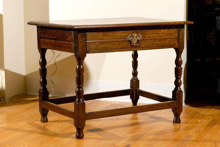 This is an English Oak side table from 1890 - 1910. Handsome turned legs with stretchers and ogee edge on top.
