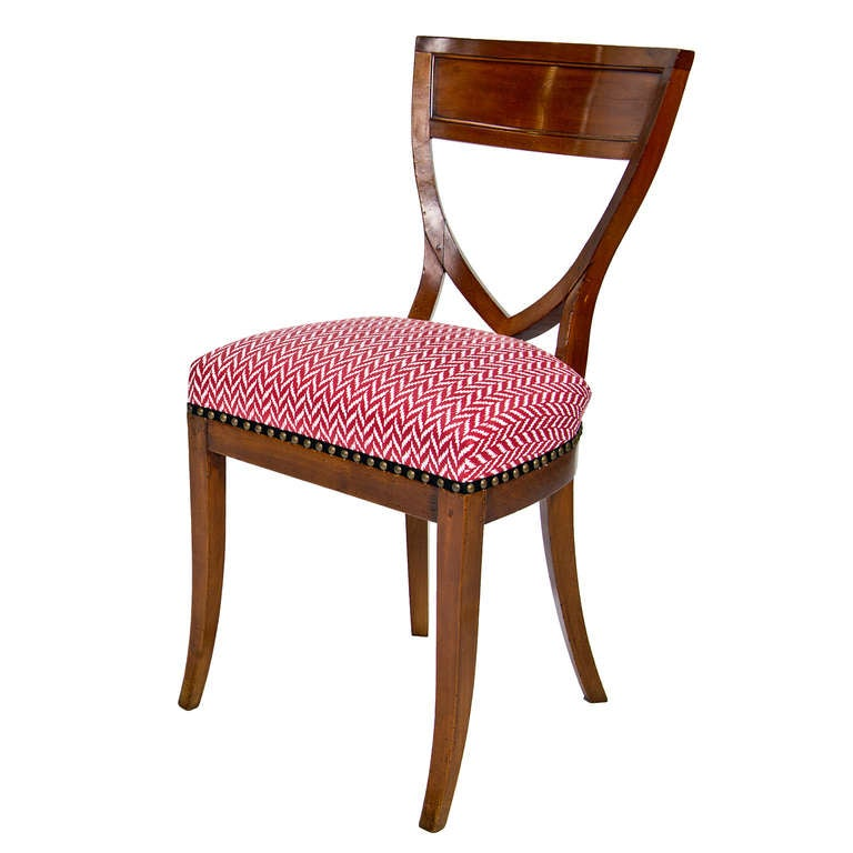 A set of six Biedermeier mahogany shield shaped back dining chairs with seats upholstered in Alessandra Branca's rouge Dudley fabric.
