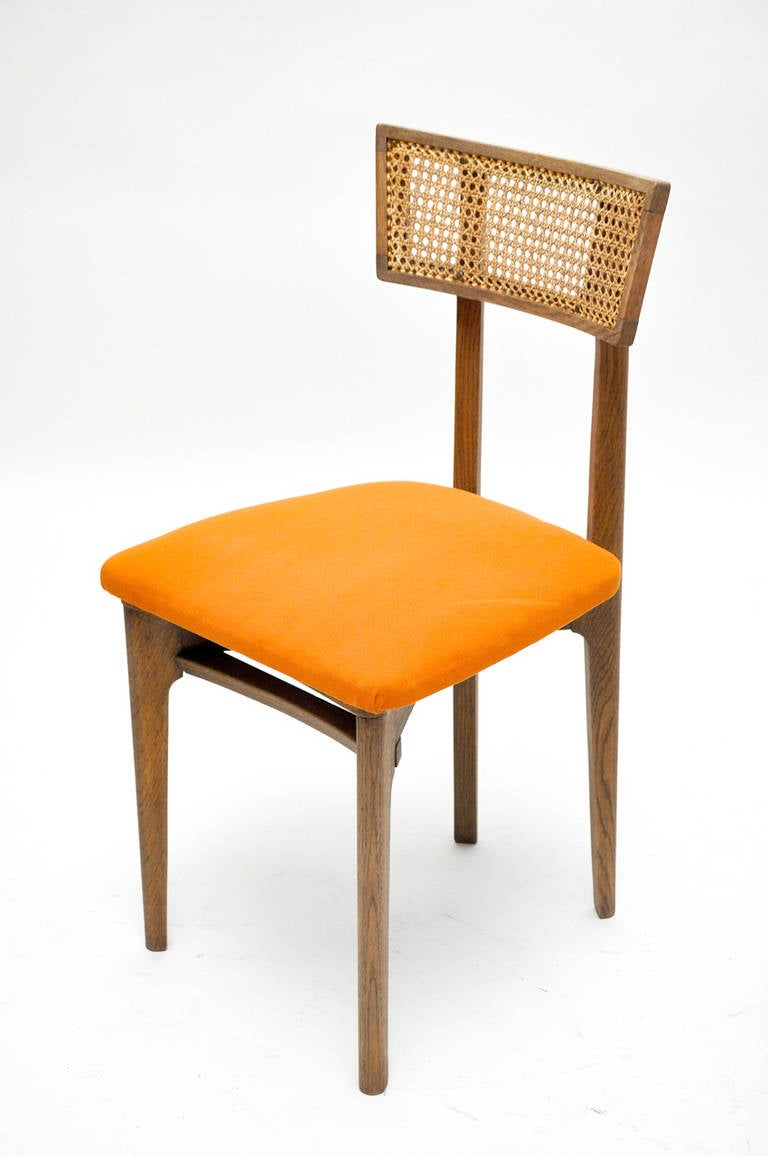 A set of six Cerused oak dining chairs with caned splats and deep orange mohair upholstered seats, in the style of Marcel Gascoin.