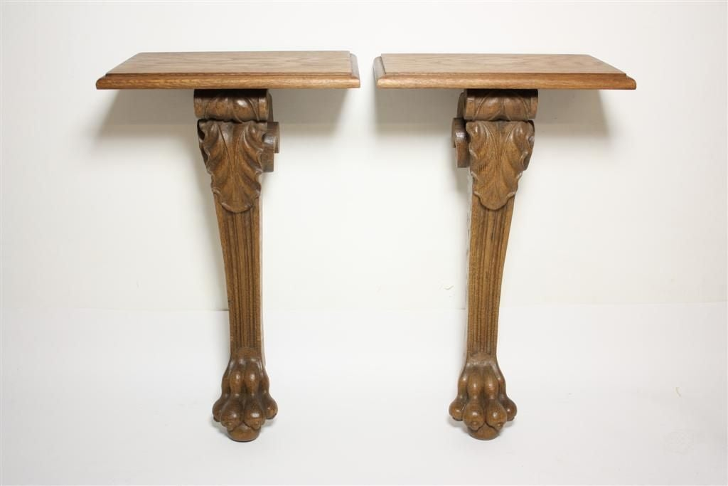 A pair of Napoleon III carved oak wall brackets featuring acanthus leaf detail at knee and pawed foot base.