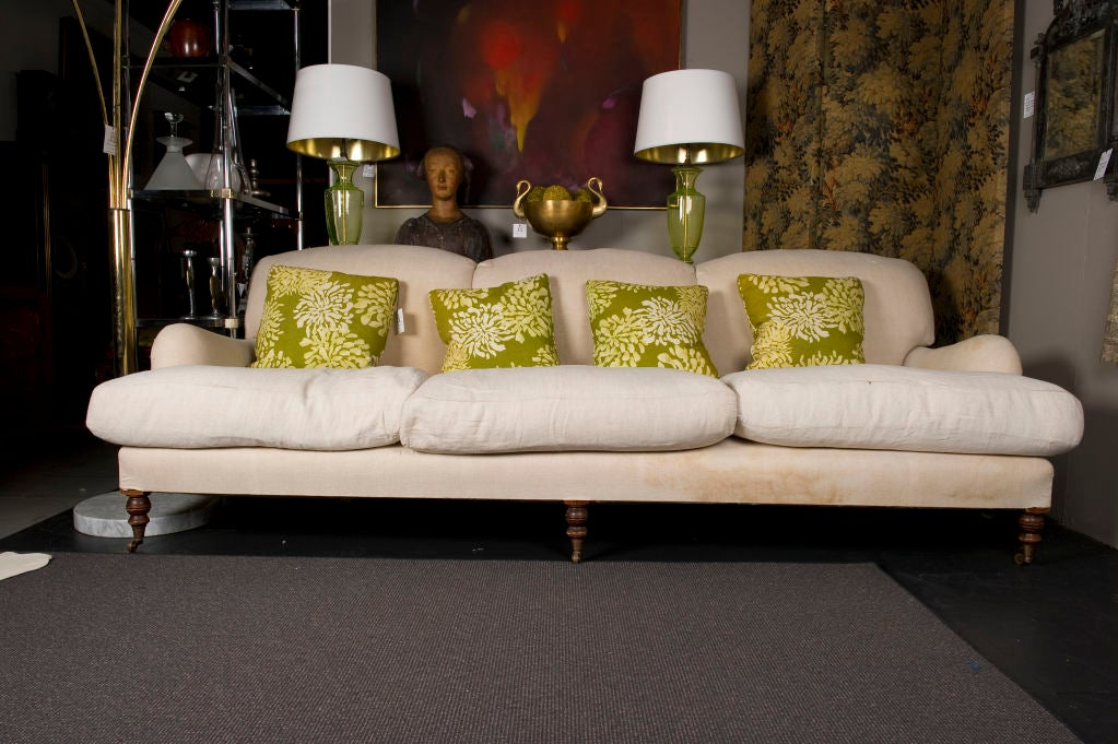 A classic 3-seat George Smith sofa --ready to be recovered. Features three feather and down seat cushions, soft upholstered tight back, brass castors on the three front legs. This sofa was bought in London from George Smith around 1985.