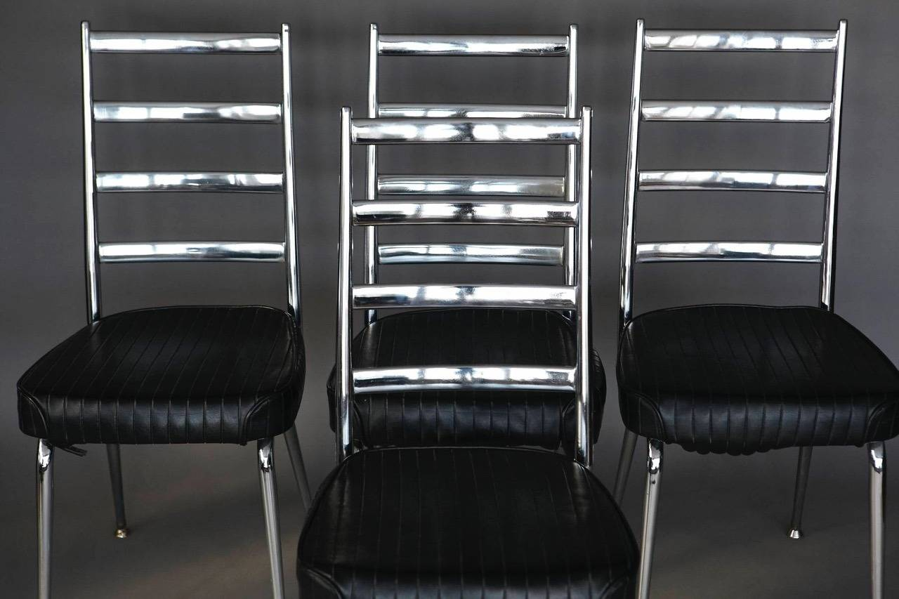 Set of four ladder back chromed dining side chairs with black vinyl upholstery by Chromecraft, circa 1960s. The chrome is in excellent condition, no rips in the original vinyl, very solid construction. Vinyl is a little loose on some chairs, but