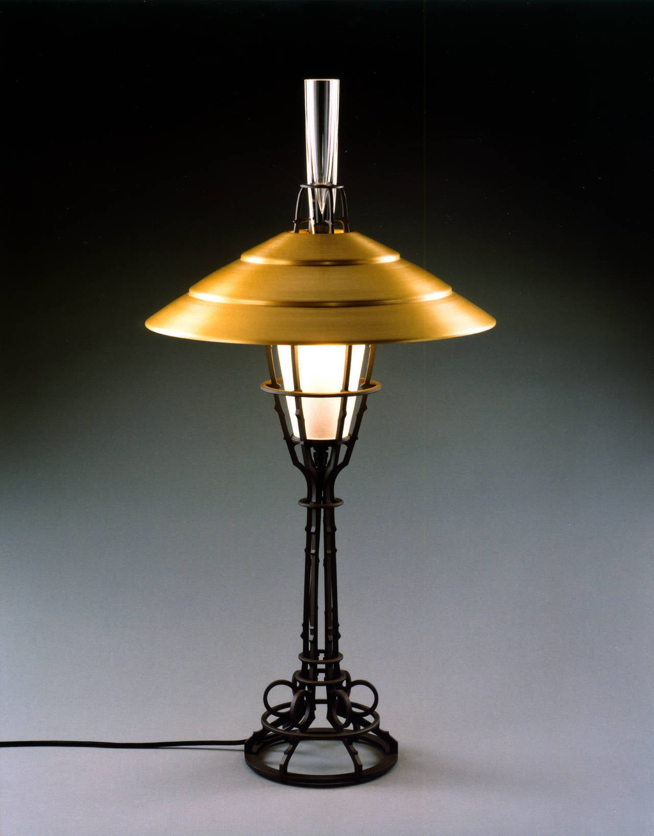 "Contemporary American metal sculptor Albert Paley's ""Corona Table Lamp"" is made of formed and fabricated blackened steel, a glass bulb shade and an aluminum shade with a glass insert. All the lamps in this series are stamped, dated and"