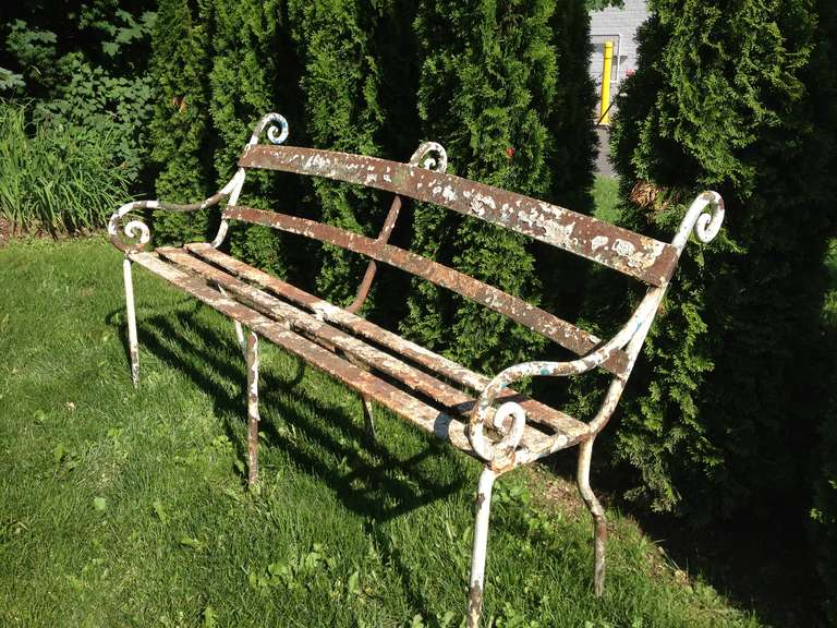This rare and exceptional late Scottish Regency bench is both elegant and whimsical. Constructed of hand-forged heavy wrought iron with remnants of old, possibly original paint. Canted seat back and bold scrolled ears and arm supports. Superb