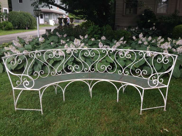 This large and commodious curved wrought iron bench is a rare find. In excellent condition with no repairs, the frame is painted white, while the seat comprises four panels of pierced sheet iron in a faded dark green color with some very minor