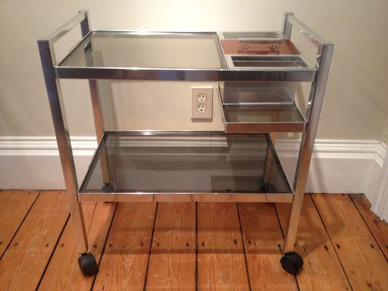 This compact Mid-Century English cocktail trolley will give you years of pleasure, especially if you are short on space but long on entertaining in style. Fashioned from chrome and smoked glass, it features a built-in ice bucket, two bottle storage