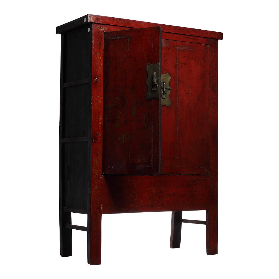 A 19th century hand-painted chinoiserie and red lacquer armoire from China. This Chinese 19th century armoire displays a red lacquer and hand-painted gilt chinoiserie designs. The rectangular armoire rests on four legs linked on the sides by two