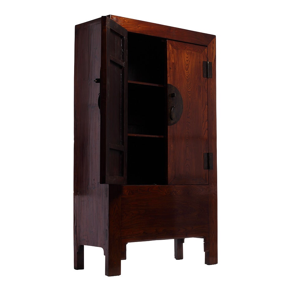 A 19th century large Chinese elm armoire with brown lacquer finish and traditional round medallion hardware. This Chinese elmwood armoire features a linear profile with clean lines beautifully enhanced by the warm finish of the brown lacquer. The