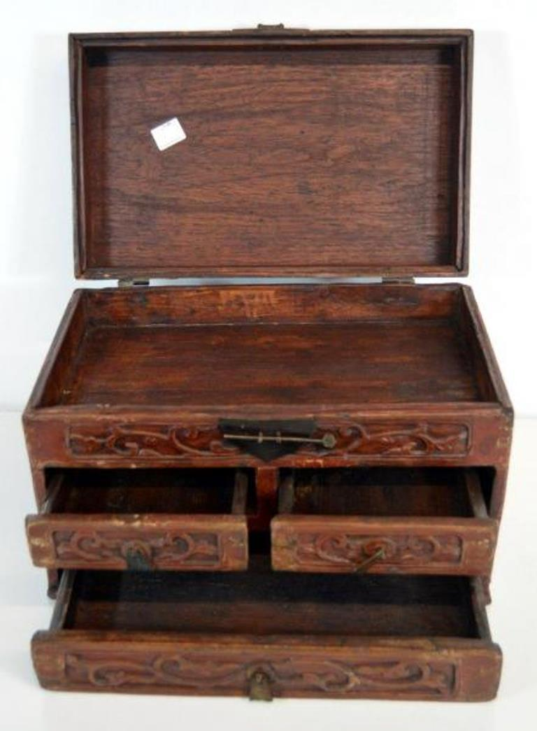 An early 20th century Chinese jewelry box made with red brown lacquered wood and iron hardware. This small rectangular box features a large bottom drawer, two smaller ones and a hinged lid. The front is blanketed with carved foliage patterns. Each