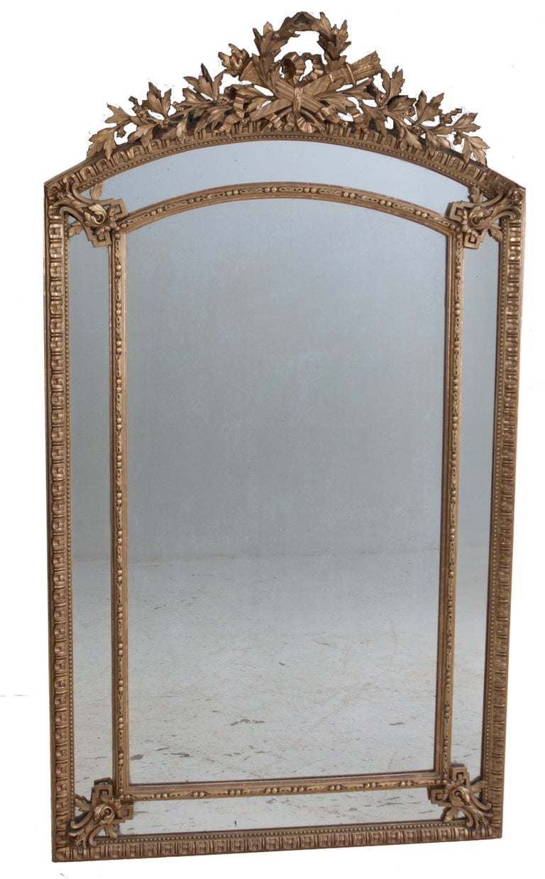 French 19th century pareclose mirror in the Louis XVI Style. The mirror is gold gilded with crossed torches with flowers and leaves adorning the cartouche. Egg and dart motif surrounds the outer mirror frame, the detail in this mirror is amazing.