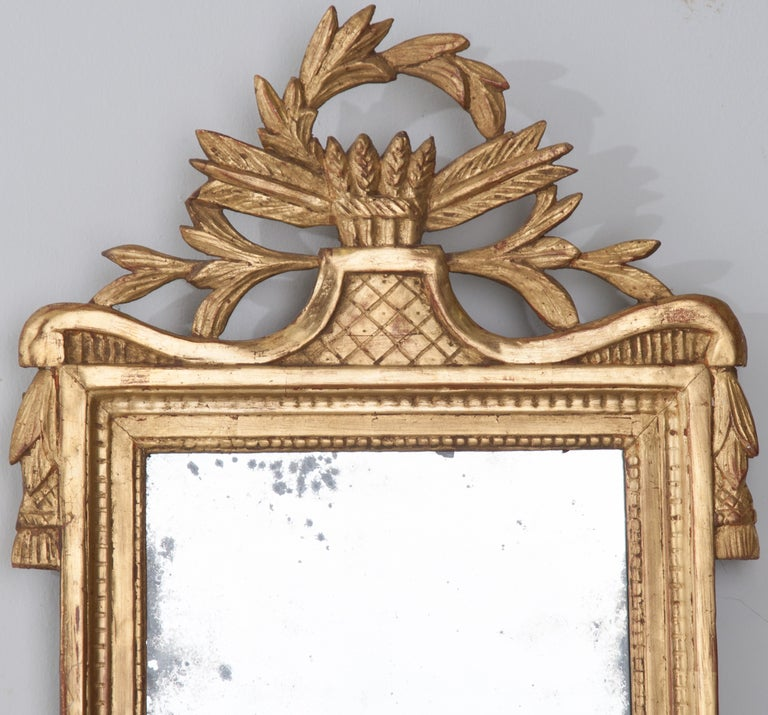 French Louis XVI style gilt-wood mirror with pierced crest depicting a wreath around arrow heads and feathers from the 1780's with original mercury mirror glass.