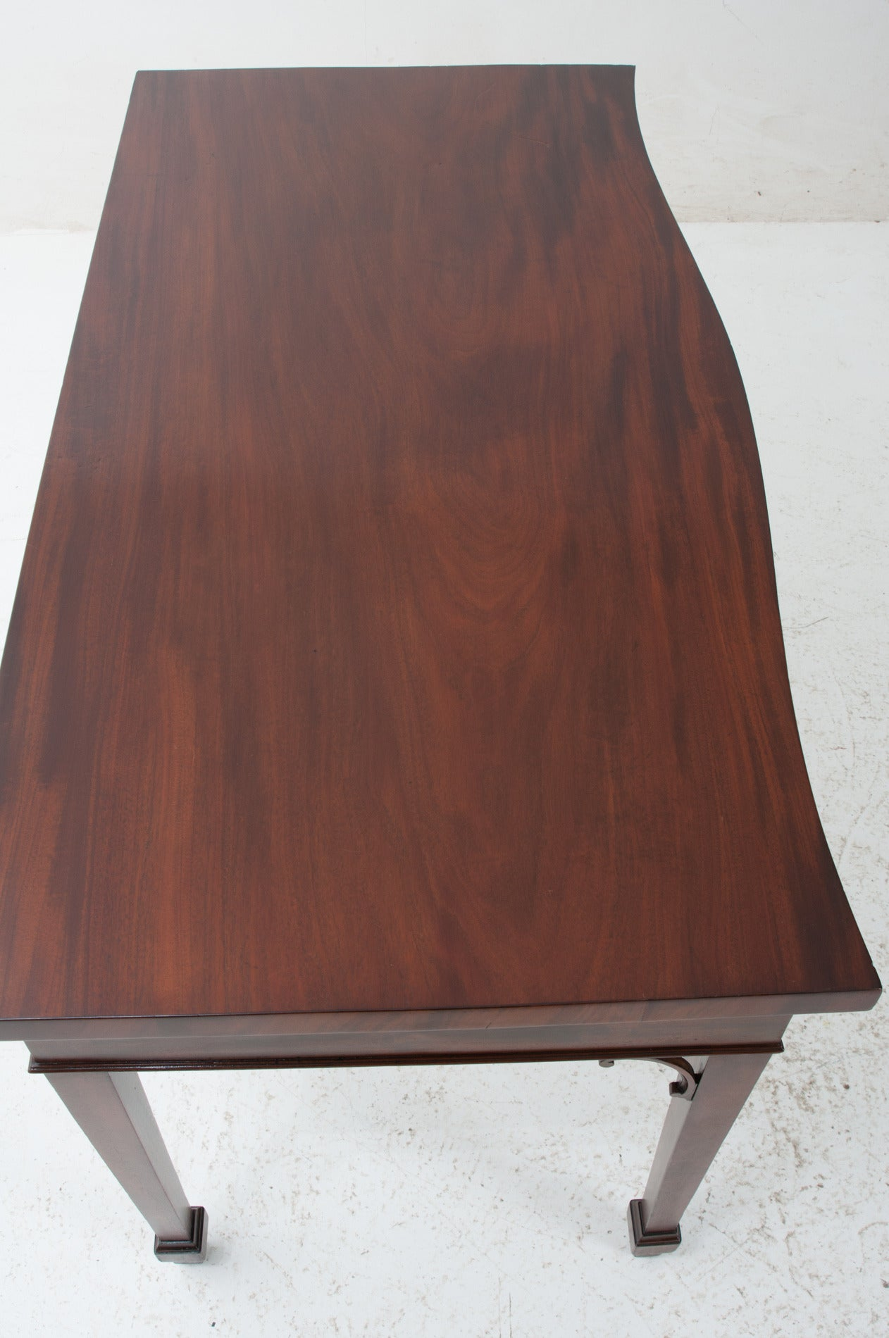 English 1860s serpentine front server or console in beautiful rich mahogany. It retains its beautiful, original color and patina and has a fresh polish. See the detailed pictures for a scratch on the surface. It doesn't steer us away, we just