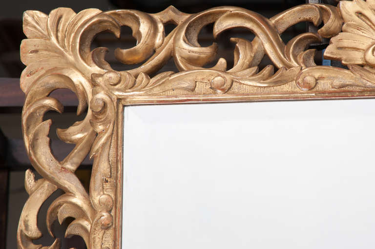 A stunning heavily carved and pierced mirror frame all gold gilt with beveled mirror glass. A statement mirror! 1840s from Italy.