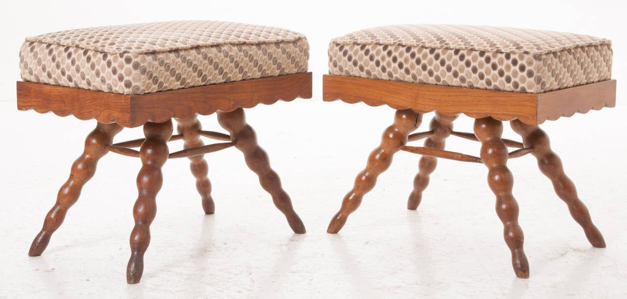 A playful pair of vintage occasional stools are in wonderful condition! Newly upholstered in fitting fabric, the seats sit over a scalloped apron with four splayed legs.