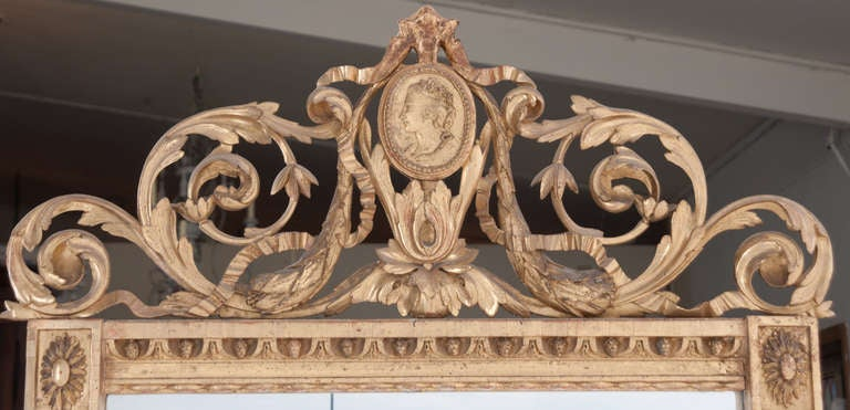 French mirror from the 1700's is all carved out of wood! A stunning mirror! The very top of this mirror has been reworked, then the ribbons start the original old wood crest which features a cameo, scrolling and carved leaves finish off the crest.