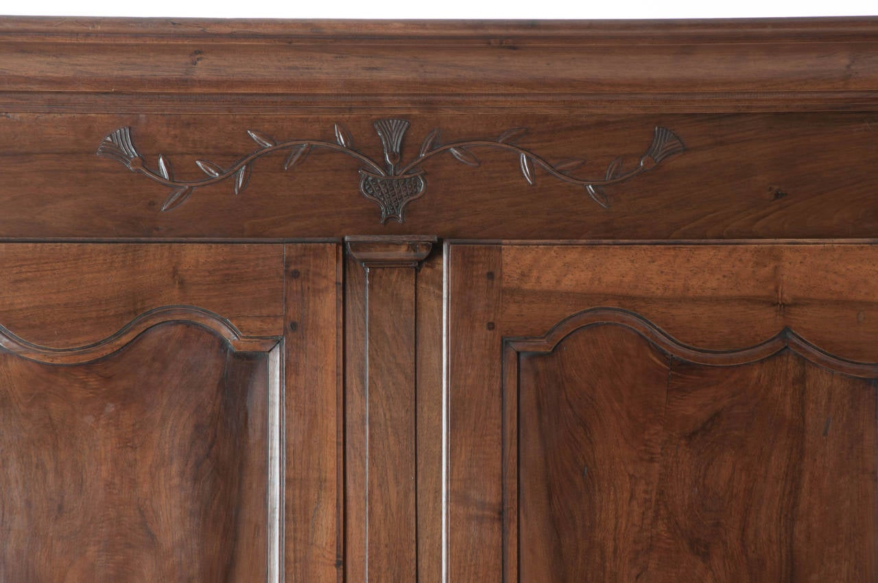 A stunning, hand-carved, solid walnut armoire in great condition! The patina and coloring of walnut are stunning with interesting and minimal carvings, all steel hardware including full barrel hinges and elaborate escutcheon plates, 1880s or