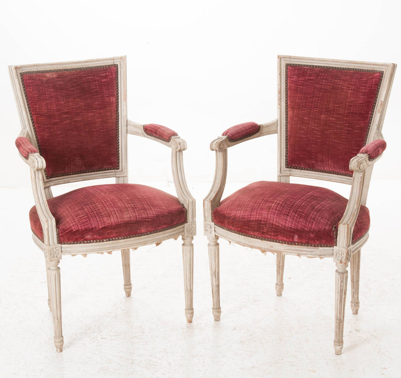 A glorious pair of Louis XVI style painted armchairs from the early 1900 with their original red velvet upholstery! The red color really make these beauties pop!