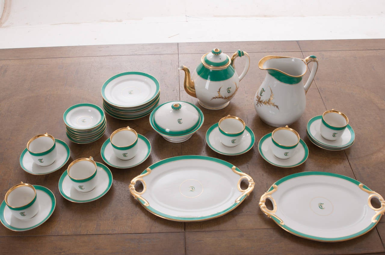 A stunning 33-piece set of Old Pairs white porcelain hand-painted and gold gilt dessert service. The letter 'T' adorns most of the pieces in this fine service from the mid-1800s. One teapot. One water pitcher. One lidded and footed bowl. Two