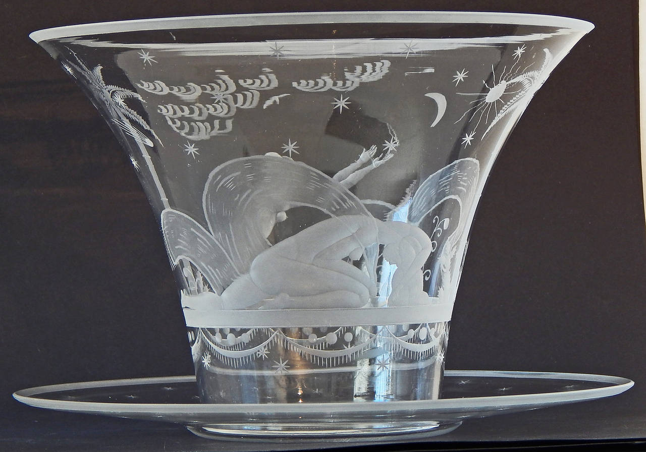 Featuring two nude female figures in an exotic setting, framed by palm trees and cactus, each reaching to or bowing before the sun and moon, this superb engraved glass vase was designed by F. Muller for one of the famed Bohemian/Czech glass makers