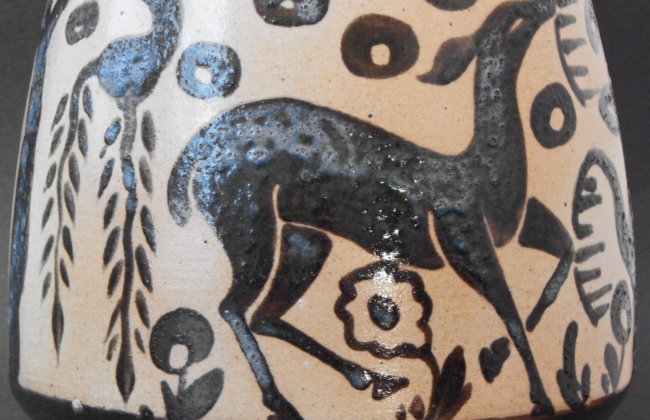 A superb example of Art Deco craftsmanship, produced by one of the world's finest workshops in the 1930s, this vase depicts a deer with lifted head, flanked by a weeping willow tree, plants with curling tendrils, and geometric forms, all executed in