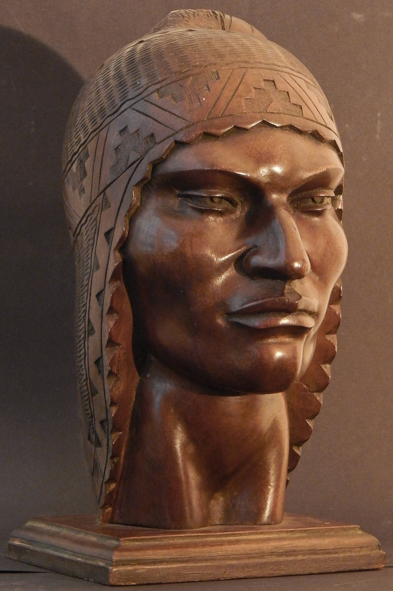 Superbly carved and visually striking, this life-size depiction of a Peruvian man in a traditional knitted headdress is a superb example of stylized Art Deco sculpture, as well as the fascination that American artists had in native cultures and